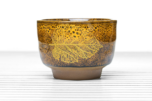 Deep Footed Tea Bowl With Speckled Yellow And Brown Glaze And Golden Leaf Pattern